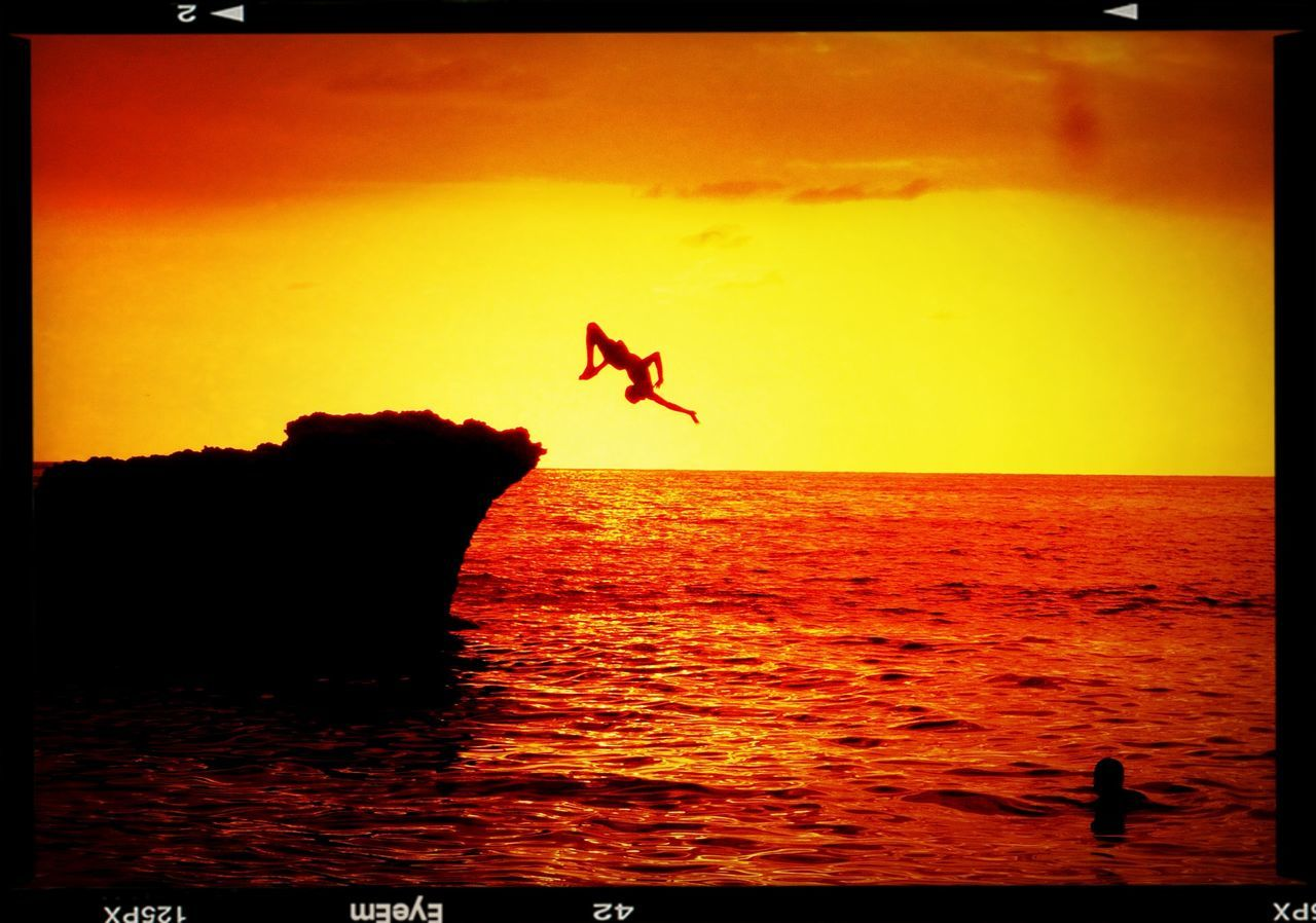Person diving into sea at sunset