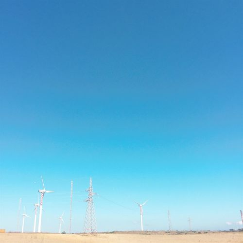 Low angle view of windmills against clear blue sky