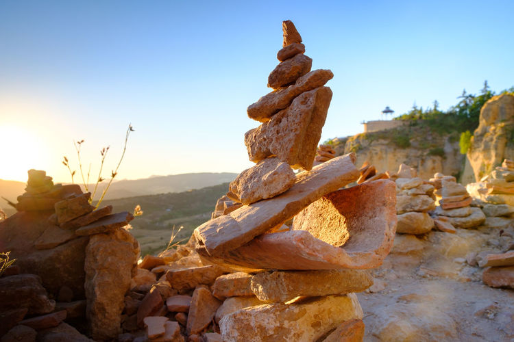Stack of rocks on land against sky