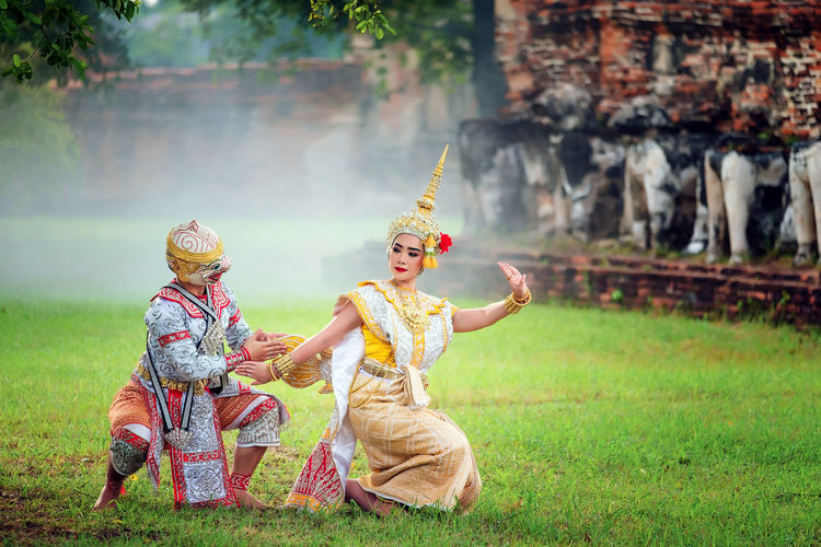 Couple performing traditional dance on grassy field