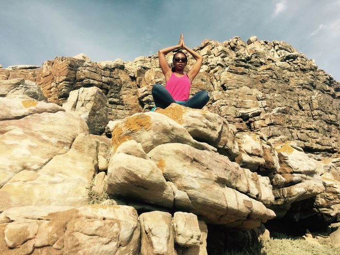 Low angle view of woman practicing yoga on rock formation