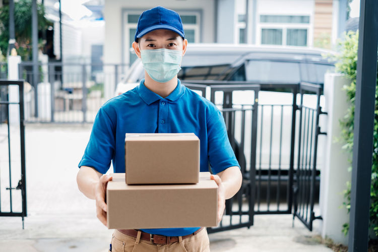 Portrait of man holding camera while standing in box