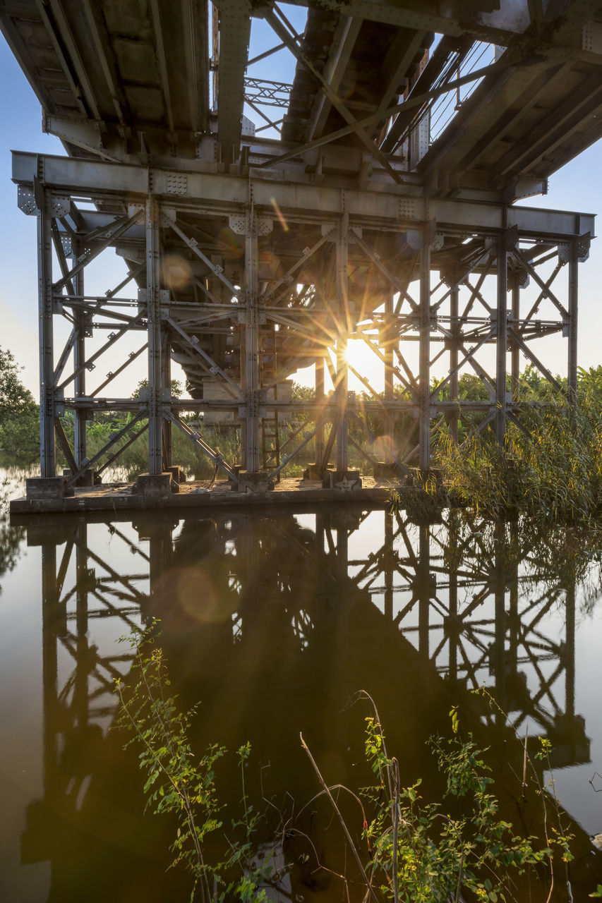 architecture, built structure, nature, no people, plant, sky, sunlight, water, day, bridge, lens flare, outdoors, connection, metal, bridge - man made structure, grass, growth, industry, sunbeam