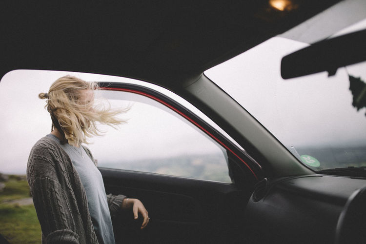 Side view of woman standing by car