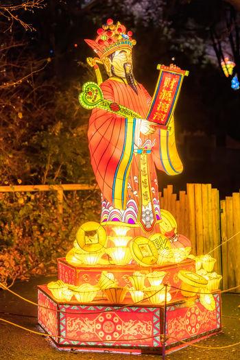 Statue of illuminated temple against building