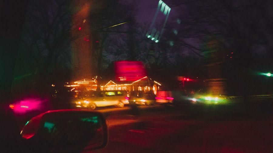Illuminated cars on road against sky at night