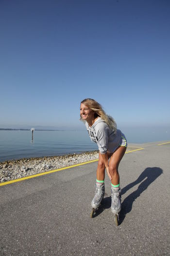 Full length of woman inline skating on road by sea against clear sky