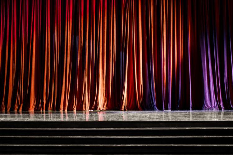 Illuminated light bulbs hanging from curtain