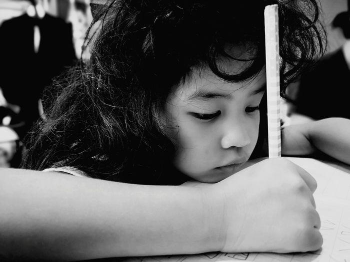 Close-up of girl writing on paper at table