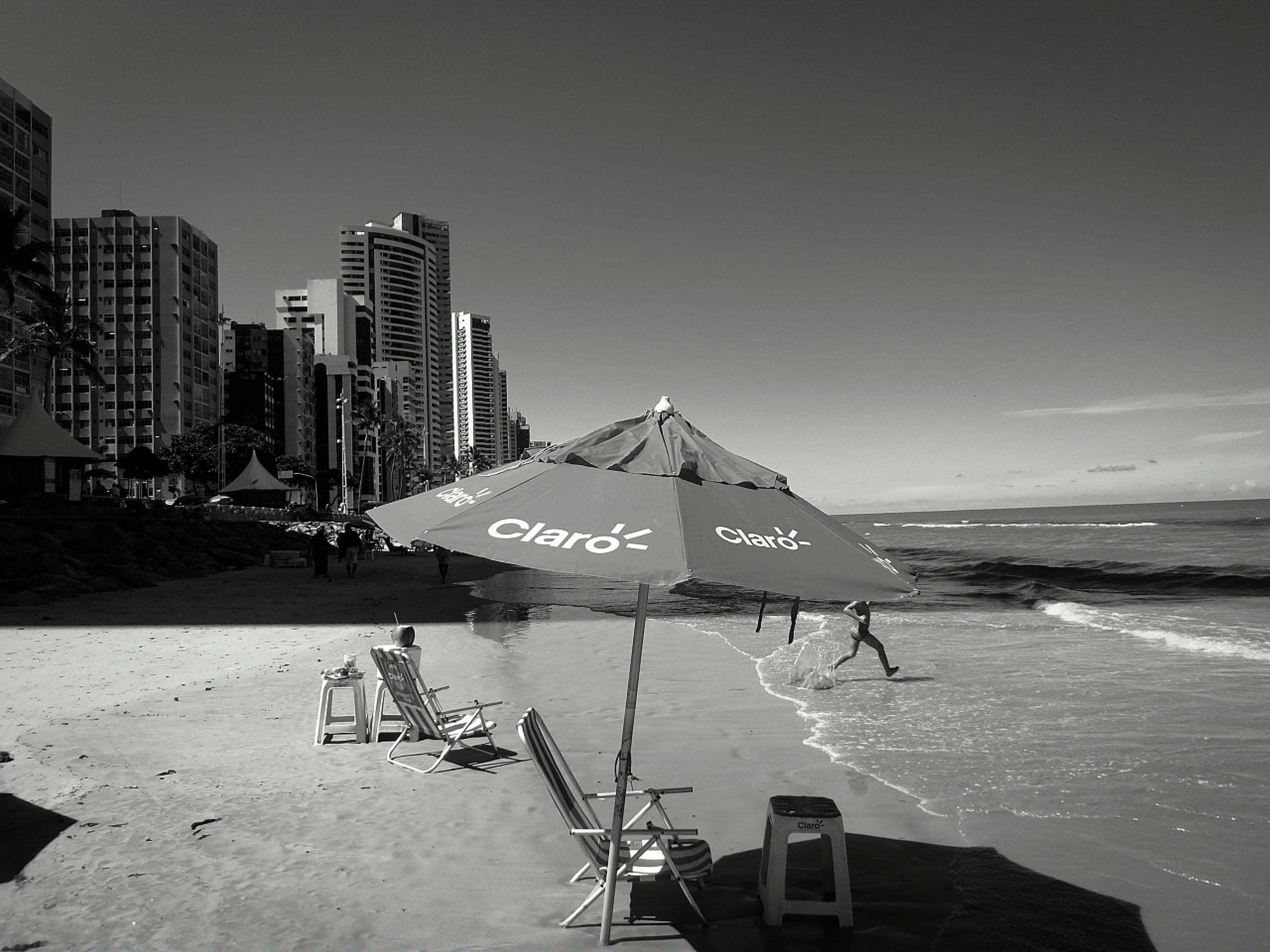 black and white, architecture, water, sky, sea, built structure, beach, building exterior, monochrome, nature, monochrome photography, city, black, land, travel destinations, building, white, urban skyline, no people, outdoors, travel, skyscraper, day, office building exterior, landscape, clear sky, sand, text, communication, sunlight