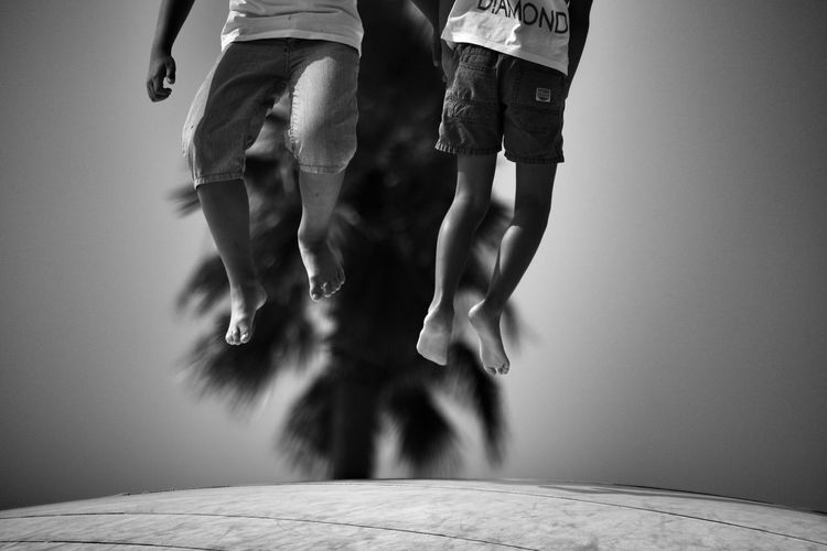 Low-Section Of Children Jumping On Roof