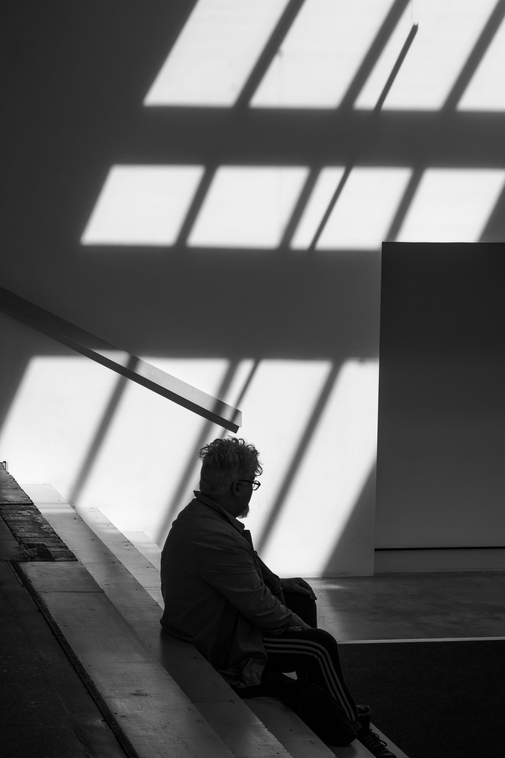 sitting, one person, side view, real people, wall - building feature, indoors, relaxation, built structure, architecture, day, home interior, sunlight, shadow, lifestyles, leisure activity, men, contemplation, clothing, adult, depression - sadness, social issues