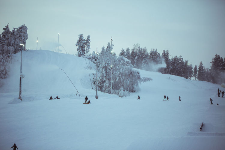 People skiing and snowboarding on snow covered land