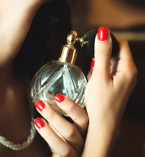 Close-up of woman holding perfume bottle
