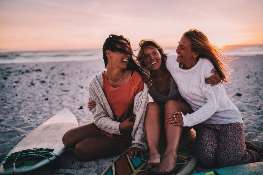 Sea Beach Water Sunset Sky Leisure Activity Friendship Emotion Togetherness Group Of People Young Women Young Adult Sitting Happiness Lifestyles Bonding Real People Teenager Horizon Over Water Positive Emotion Outdoors