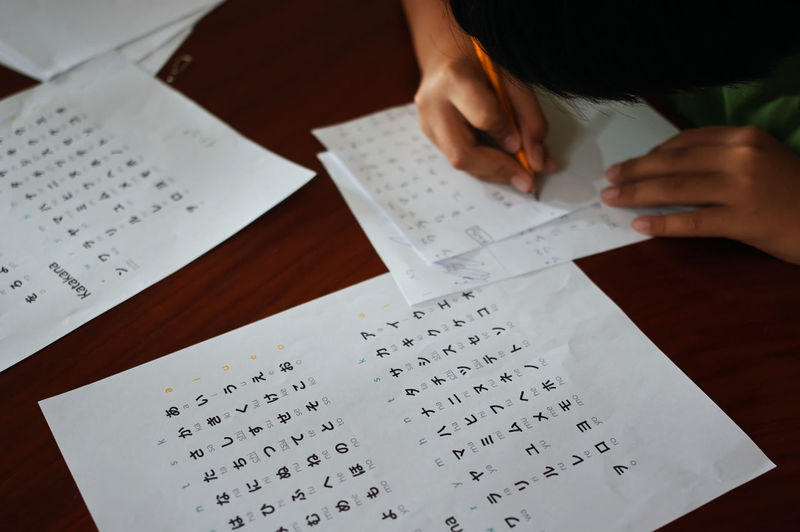 Cropped hands of boy writing in paper