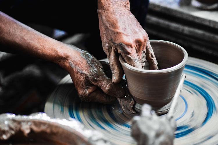 Cropped hands of man making pot in workshop
