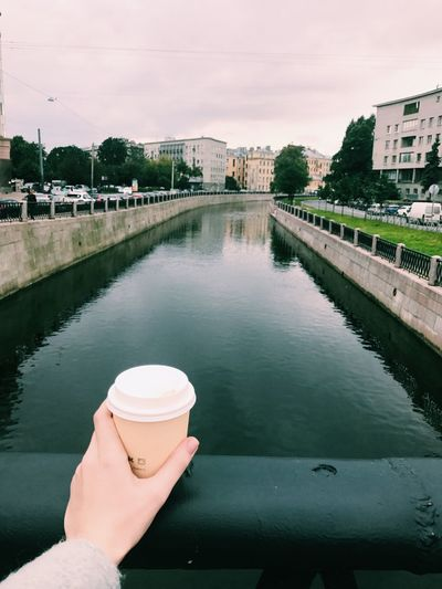 Human Hand Human Body Part Real People Architecture Built Structure Water Human Finger One Person River Personal Perspective Unrecognizable Person Building Exterior Holding Bridge - Man Made Structure Connection Outdoors Lifestyles Day City Sky Coffee Coffee Time Coffee Cup Coffee - Drink