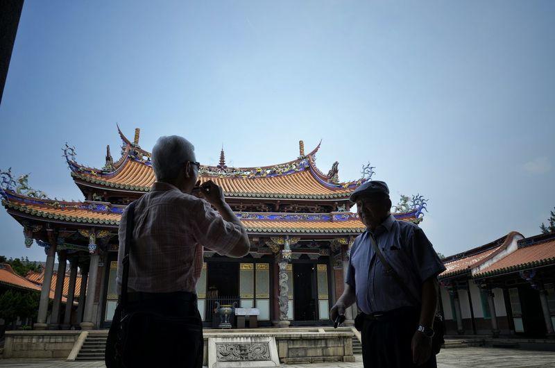 Senior men standing in temple against clear sky