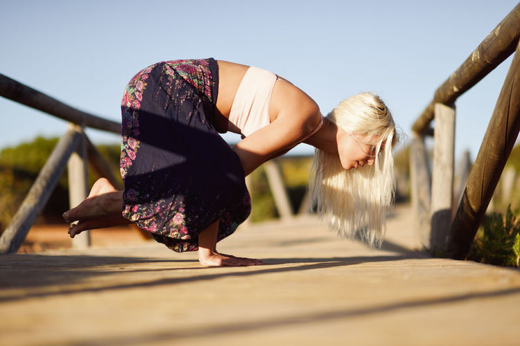 Woman enjoying the sunset on a beautiful beach in Cadiz, Andalusia, Spain. Caucasian female practicing yoga on wooden bridge. Real People Lifestyles Women Wood - Material One Person Leisure Activity Selective Focus Blond Hair Day Sky Nature Adult Sunlight Child Hair Females Casual Clothing Side View Hairstyle Outdoors Yoga Sport
