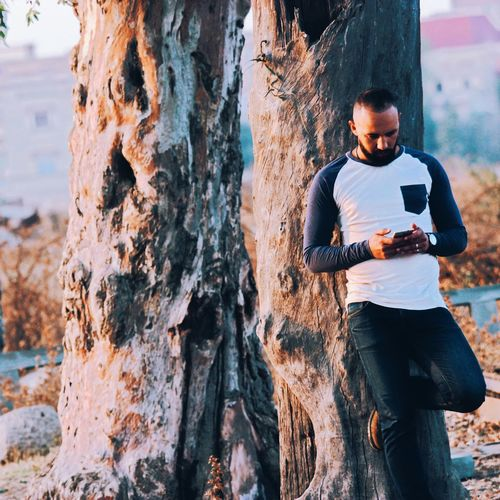 Young man using phone while standing against tree trunk