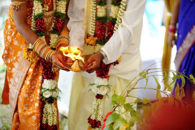Midsection Of Couple Holding Diya During Wedding Ceremony