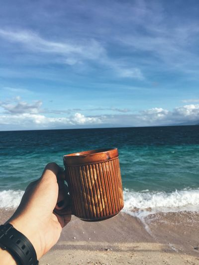 Cropped hand holding coffee cup at beach against sky