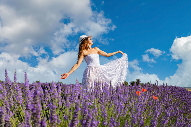 Young woman with long brown hair singing and dancing in a lavender field.