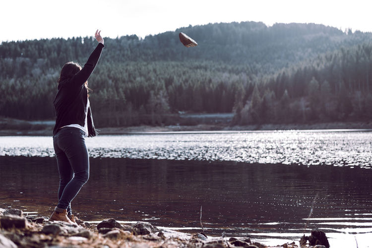 Side View Of Woman Throwing Stone In Lake