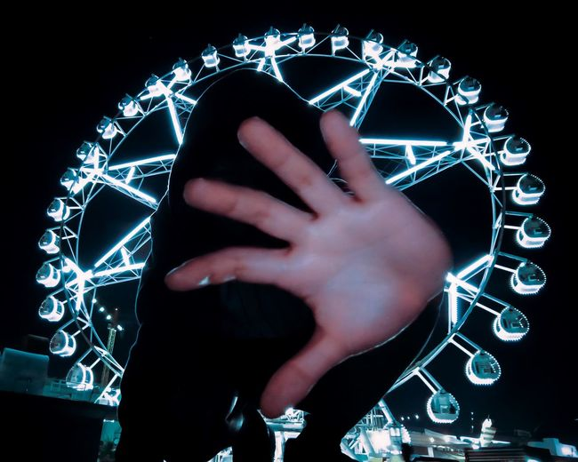 Close-up of hand using smart phone against black background