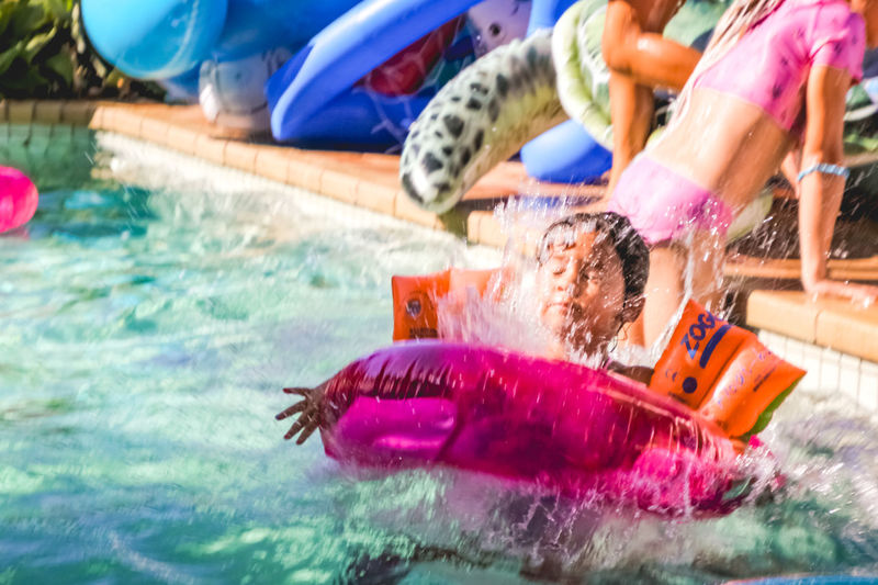 Little girl wearing floaties and inflatable ring jumping in the pool causing a splash Water Pool Swimming Pool Swimming Child Nature Motion Fun Enjoyment Childhood Group Of People Inflatable  Multi Colored Women Real People Offspring Leisure Activity Emotion Floating On Water Splash Inflatable Ring