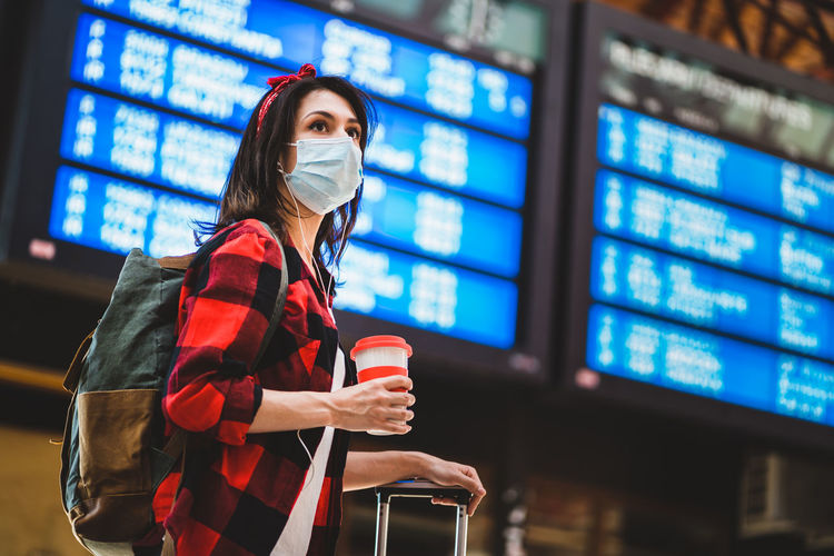 Young woman wearing mask looking away while standing at airport