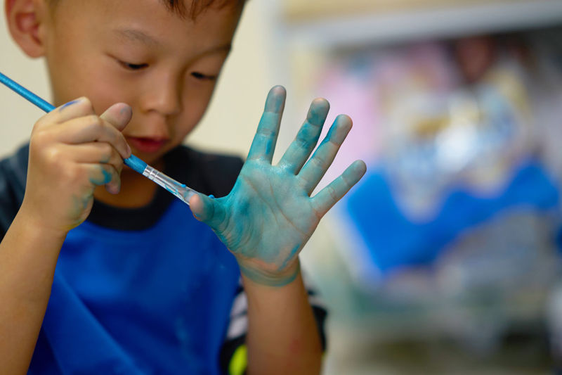 Cute boy painting hand