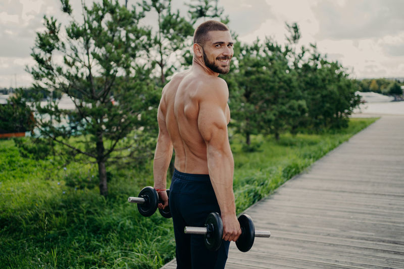 Portrait of shirtless man lifting dumbbells in park