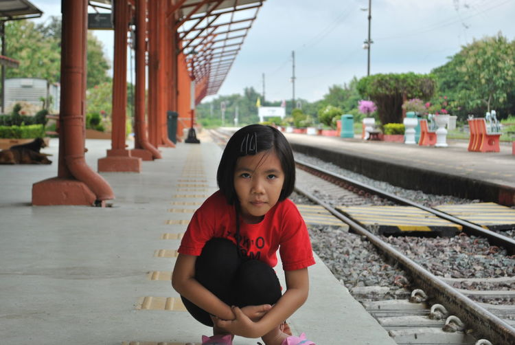 Portrait of girl crouching on railroad station platform