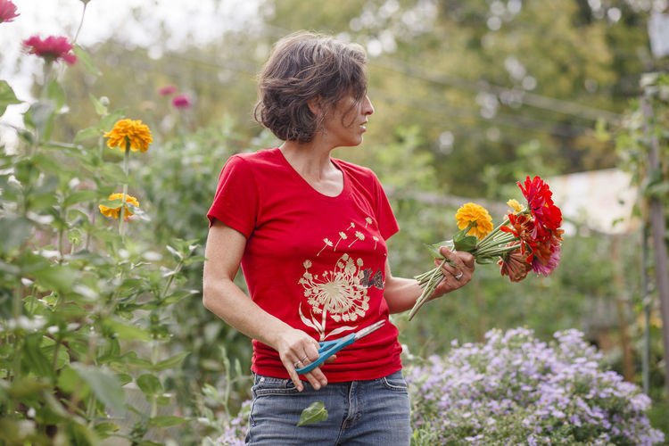 Full length of a woman holding red flowering plants