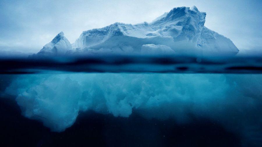 Iceberg floating on sea against sky