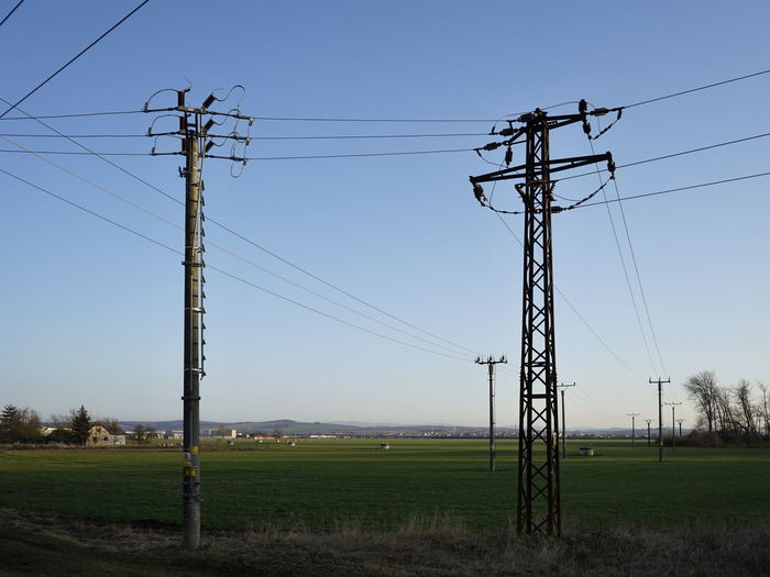 Electricity pylon on field against clear sky