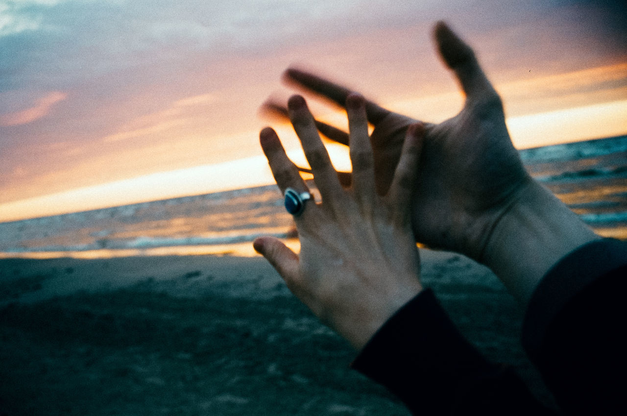 Cropped hands of man and woman at beach against cloudy sky during sunset