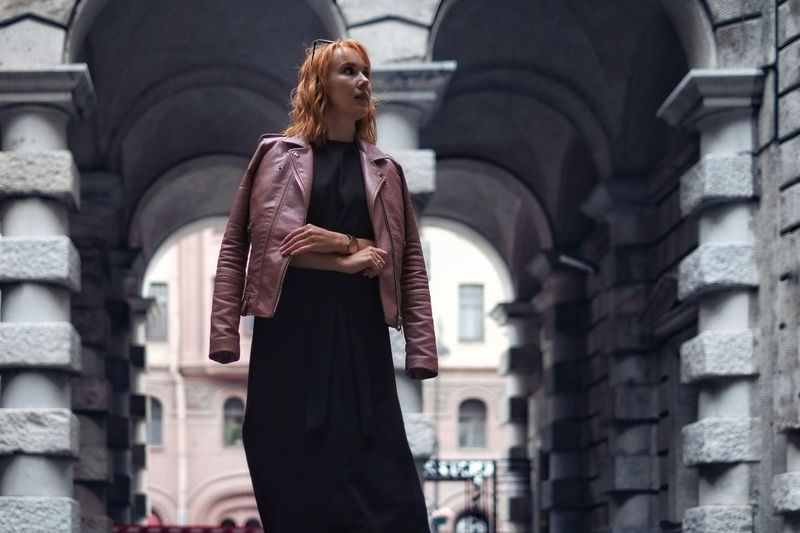 Low angle view of woman wearing jacket while standing against arch
