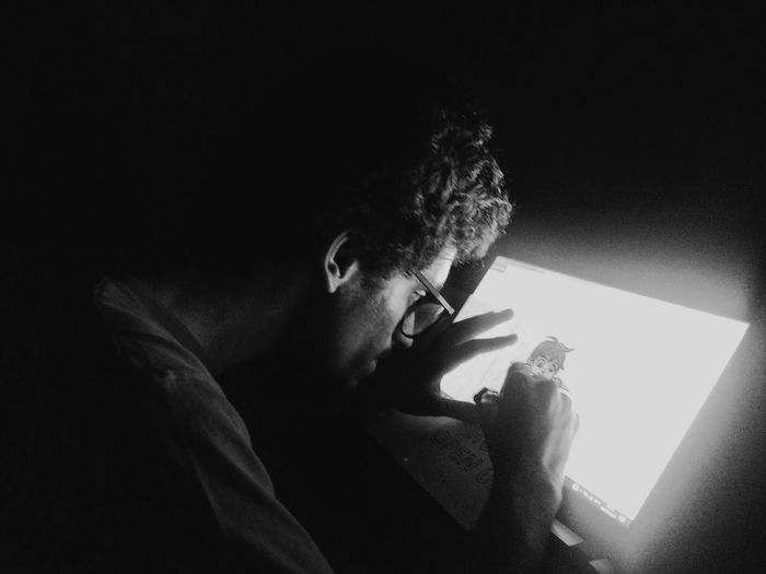 Portrait of young man holding paper in darkroom