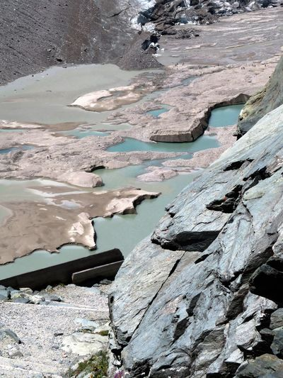 High angle view of water and rock formations at grossglockner during sunny day