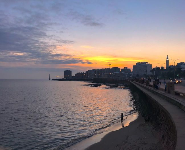 Sea And Buildings Against Sky During Sunset