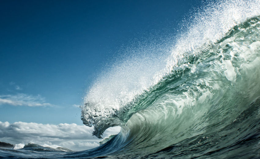 Close-up of wave rushing at shore against sky
