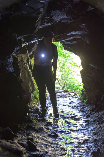 Full length of woman standing in cave