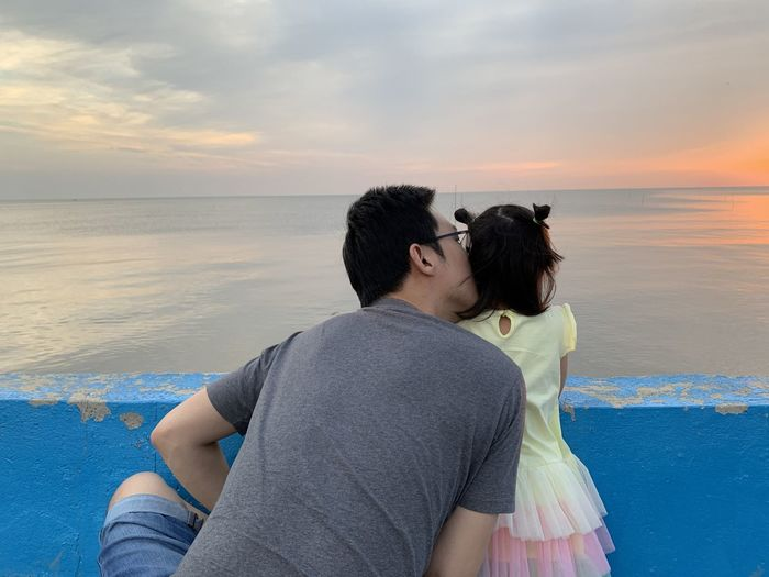 Rear view of father kissing daughter against sea during sunset