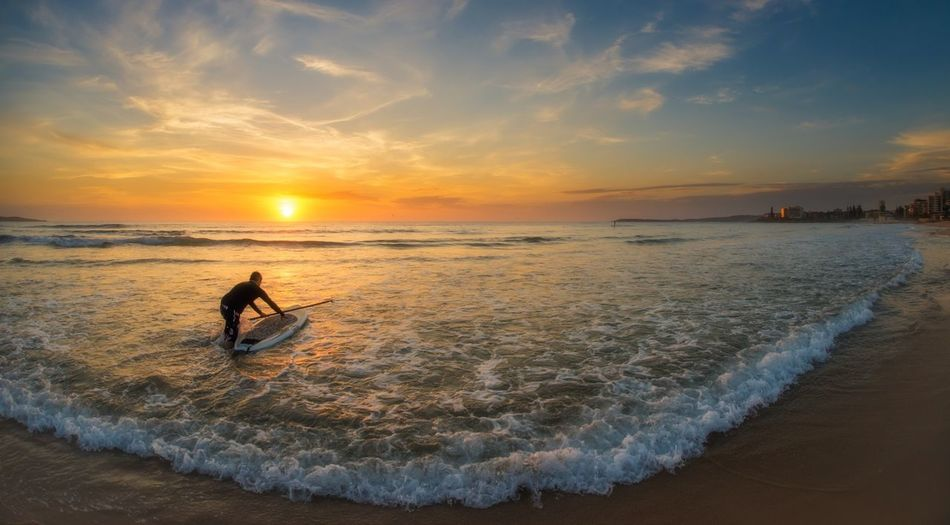 Man preparing for surfboarding on beach during sunset