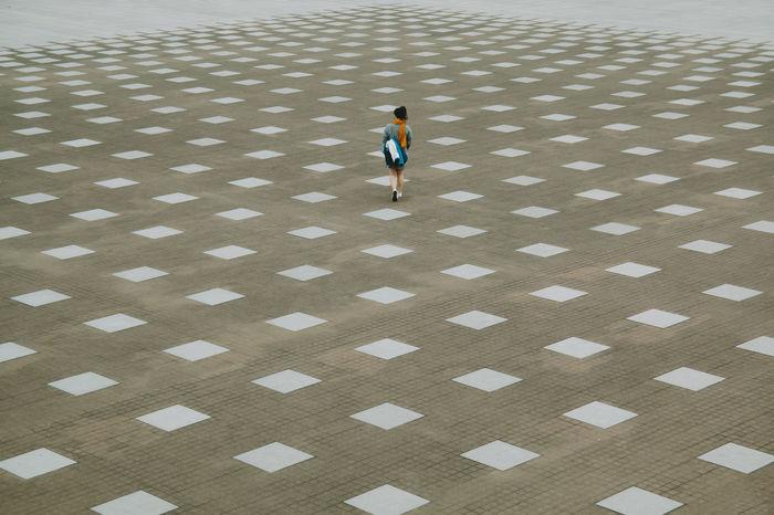 Full length of woman walking on pavement