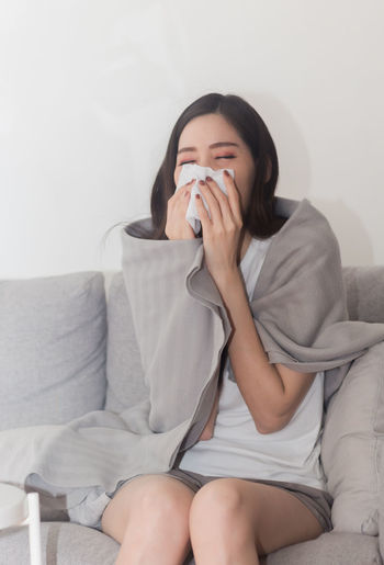 Young woman blowing nose on sofa at home