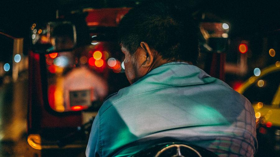 Rear view of man driving jinrikisha at night